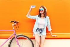 使用相当微笑的少妇采取在智能手机的自画象有在五颜六色的桔子的减速火箭的自行车的 免版税库存照片