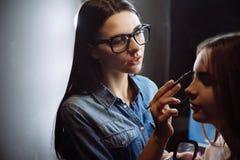 使用眼眉刷子的好的悦目visagiste 库存图片