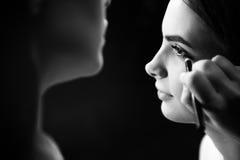 使用眼线膏的专业女性visagiste 免版税库存图片