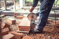 使用研磨机的建筑工人为切开的和锯的建筑砖 库存照片