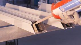 使用硅树脂管的工作者的手为修理窗口室内 从铝的窗口细节 建筑查出的好成套装备工作者 免版税库存图片