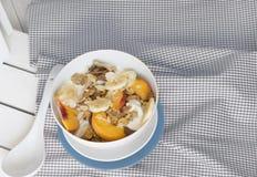 使用碗谷物和果子在橙色桌布 库存照片