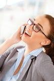 使用移动电话的可爱的女实业家 免版税库存照片