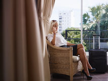 使用移动电话的女实业家在旅馆客房 免版税图库摄影