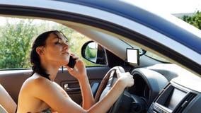 使用移动电话的妇女驱动器 免版税库存图片