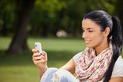 使用移动电话的少妇在公园微笑 免版税图库摄影