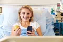 使用移动电话的少年女性患者在医院病床 免版税库存图片