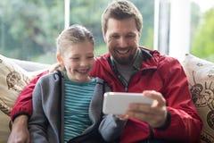 使用移动电话的父亲和女儿 图库摄影