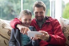 使用移动电话的父亲和女儿 免版税库存照片