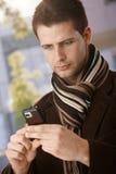 使用移动电话的英俊的人 免版税图库摄影