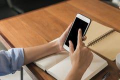 使用空白的黑屏幕的少妇智能手机嘲笑,当她工作在一warmlight天时盖的商店 库存图片