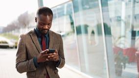 使用站立在办公楼附近的智能手机的愉快的非裔美国人的商人 事务,人们,通信 影视素材