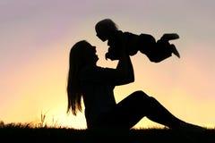 使用笑的母亲和的婴孩剪影外面 库存照片