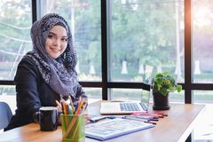使用笔片剂和膝上型计算机的美丽的年轻回教创造性的设计师妇女 免版税图库摄影