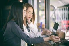 使用笔记本工作和讨论o的两个亚裔女商人 库存图片