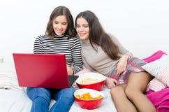 使用笔记本的两个十几岁的女孩和吃快餐,当坐时 库存照片