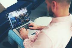 使用笔记本的商人在咖啡馆或办公室大厅 免版税图库摄影