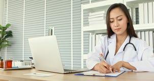 使用笔记本的悦目女性医生检查的她的耐心病症历史的医院 股票录像
