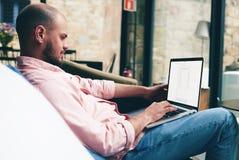使用笔记本的成功的自由职业者在看起来现代的内部对他的工作喜欢和满意 免版税库存照片