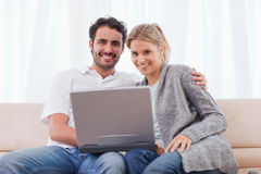 使用笔记本的新夫妇 免版税库存照片