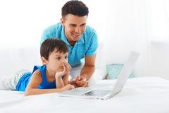 使用笔记本的爸爸和儿子在卧室 库存照片