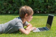 使用笔记本的男孩在室外 免版税库存图片