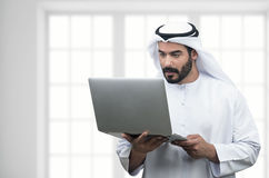 使用笔记本的阿拉伯商人在一个现代办公室 免版税库存照片