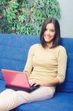 使用笔记本的年轻微笑的女孩,当在家时坐长沙发 库存图片