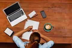 使用笔记本计算机的妇女,采取笔记在咖啡馆 工作 免版税库存图片
