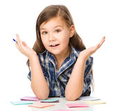 使用笔,女孩在颜色贴纸书写 免版税图库摄影