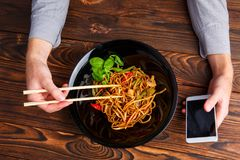 使用筷子和电话的一只人` s手 特写镜头 免版税库存照片