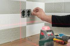 使用红外激光水平的电工安装电子出口 整修和建筑在厨房里 免版税库存图片