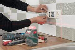 使用红外激光水平的电工安装电子出口 整修和建筑在厨房里 库存图片