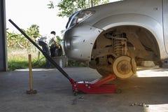 使用红色起重器,技工去除卡车轮胎 免版税库存图片