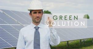 使用纯净的可再造能源,关于太阳光致电压的盘区的一位未来派技术专家,选择`绿色解答`作用 的treadled 免版税库存图片