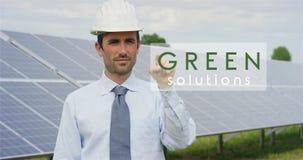使用纯净的可再造能源,关于太阳光致电压的盘区的一位未来派技术专家,选择`绿色解答`作用 的treadled 库存图片