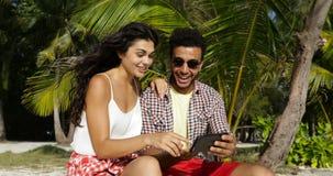 使用细胞巧妙的电话的夫妇拍Selfie照片户外在海滩、愉快的微笑的男人和妇女的棕榈树下 股票录像