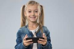 使用细胞巧妙的电话,小孩子愉快的微笑的孩子的小十几岁的女孩 免版税库存照片