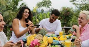 使用细胞聪明电话谈话的人们吃健康素食食物,朋友通信坐热带大阳台 股票视频