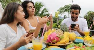 使用细胞聪明电话谈话的人们吃健康素食食物,朋友通信坐热带大阳台 影视素材