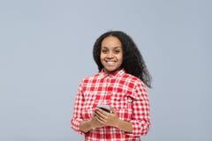 使用细胞聪明的电话非裔美国人的女孩愉快的微笑的少妇在网上聊天 免版税库存照片