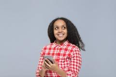 使用细胞聪明的电话非裔美国人的女孩愉快的微笑的少妇查寻复制空间 免版税库存照片