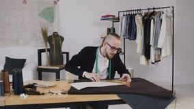 使用统治者的年轻有胡子的时装设计师凹道剪影,删去了未来衣裳的布料 织品,样式和缝合 股票录像