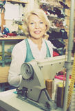 使用缝纫机的友好的成熟妇女裁缝 免版税库存照片