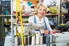使用缝纫机的可爱的成熟妇女裁缝 图库摄影