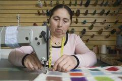 使用缝纫机的妇女在洗衣店 免版税库存图片