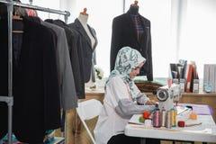 使用缝纫机的妇女裁缝 免版税库存图片