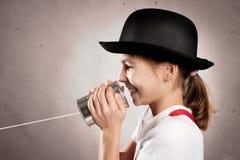使用罐头的女孩作为电话 免版税库存图片