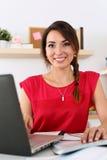 使用网上教育服务的美丽的微笑的女学生 免版税库存照片