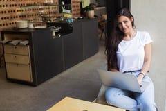 使用网书的华美的女性自由职业者为距离工作,当坐在现代咖啡店时 库存照片